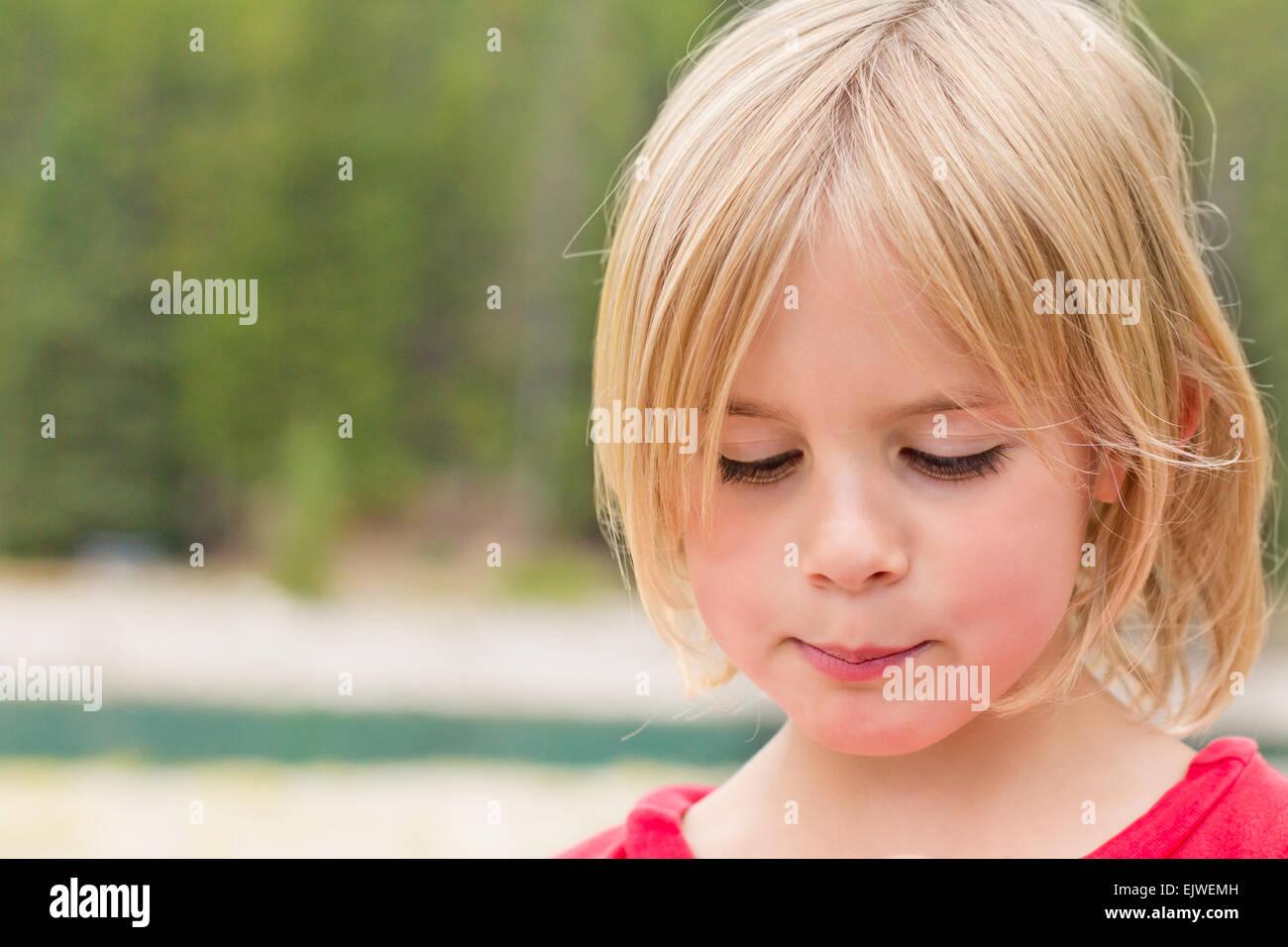 Petite fille timide à la recherche vers le bas avec un regard timide Banque D'Images