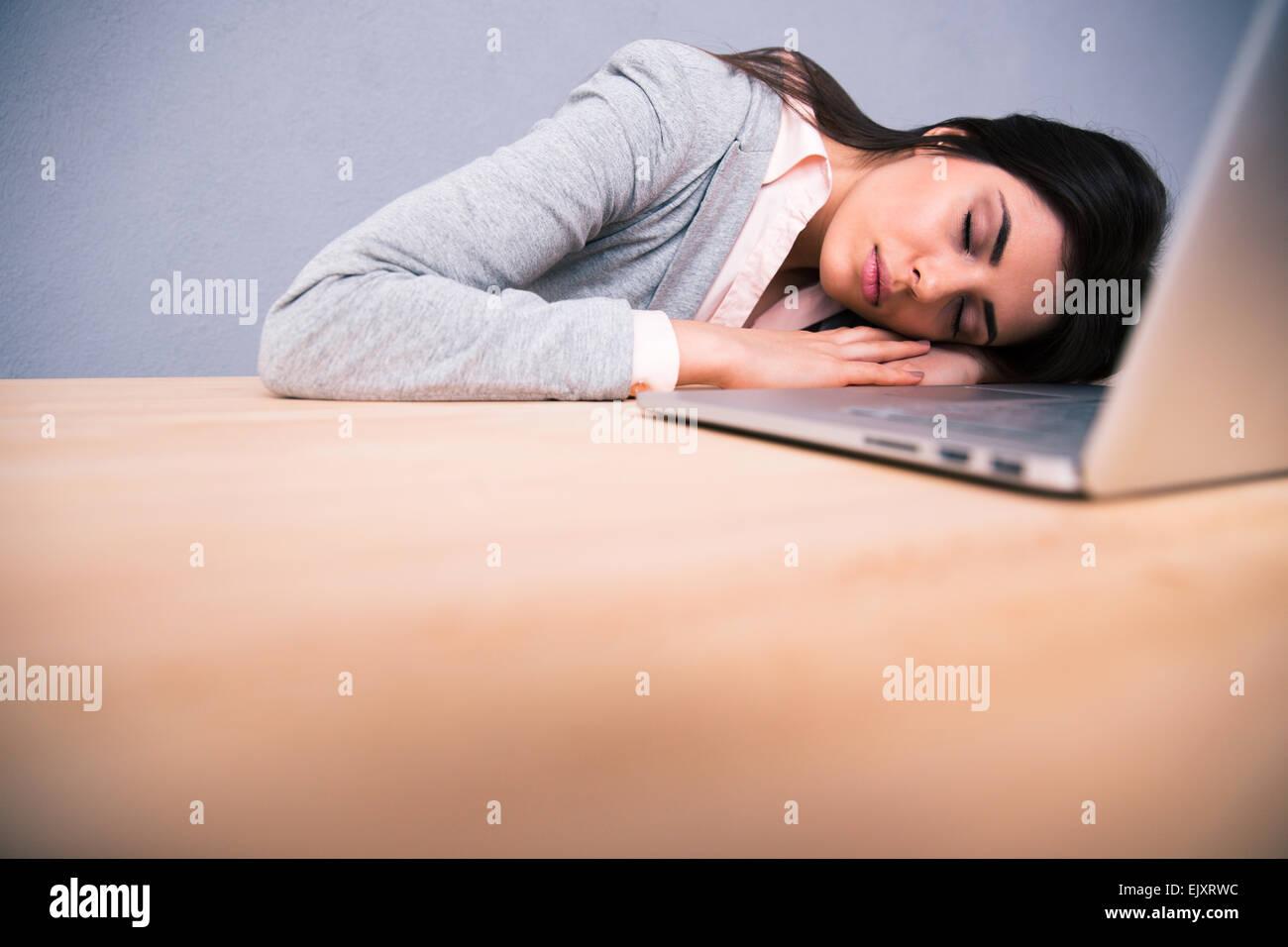 Jeune jolie femme dormir sur la table with laptop Photo Stock