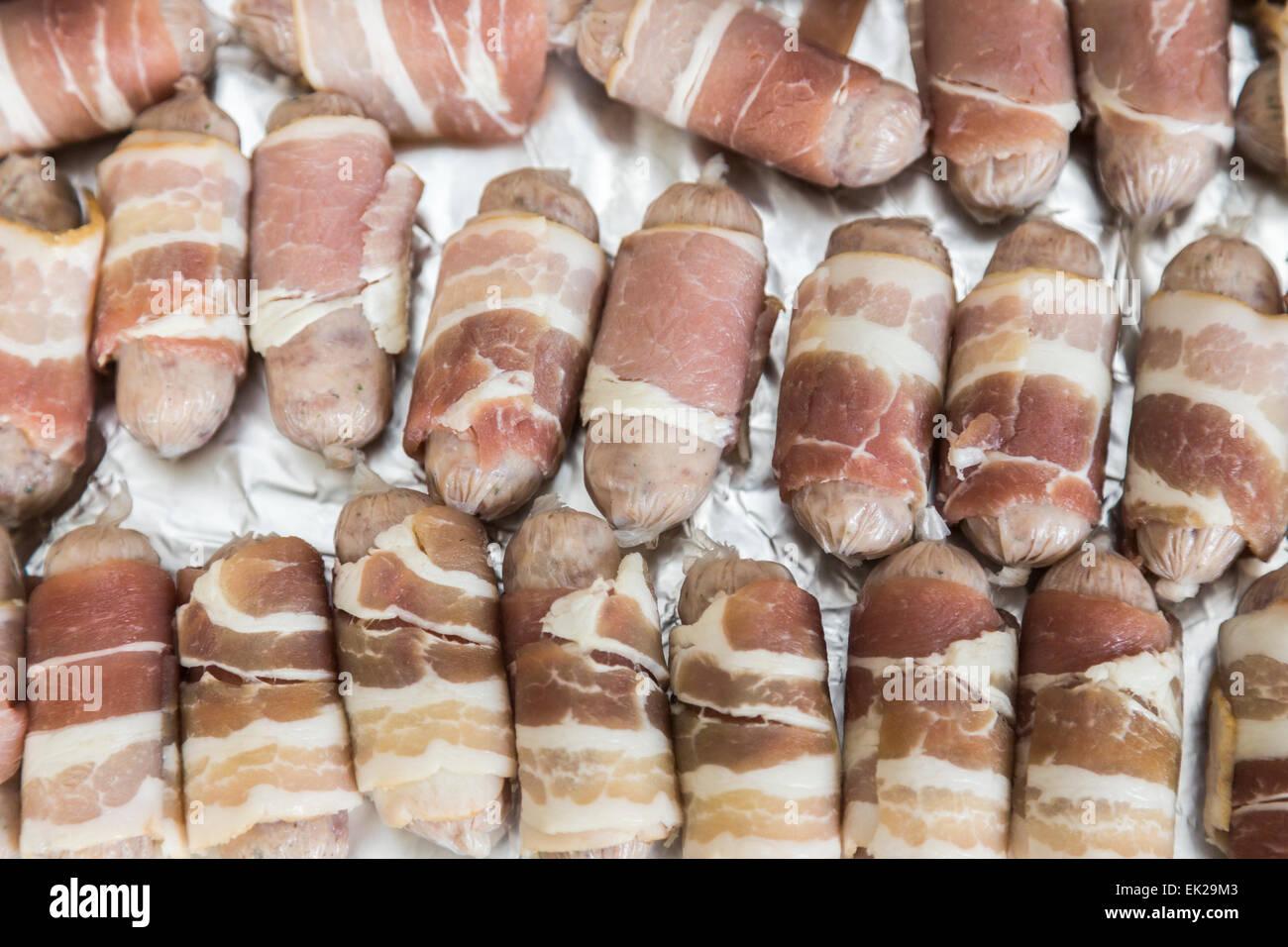Le bac intérieur en aluminium avec saucisses crues enrobé de bacon (porcs dans des couvertures) prête pour la cuisson, Banque D'Images