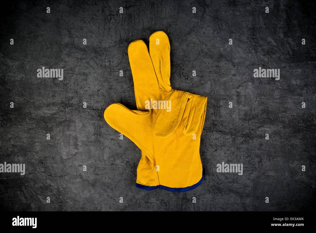 Ingénieur en construction ou en cuir jaune Builder Gants de protection de travail en faisant trois doigts geste. Photo Stock