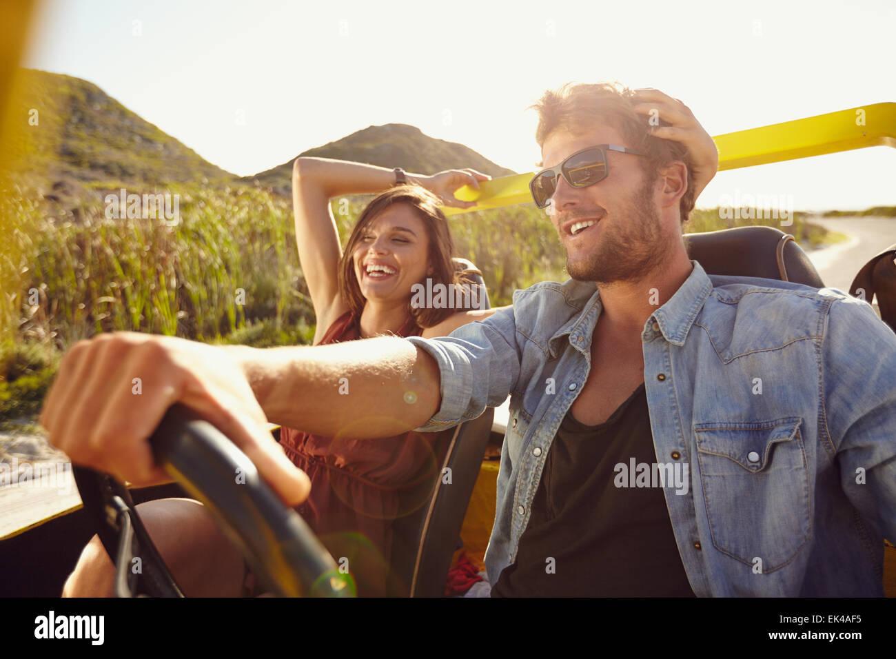 Cheerful young couple on road trip. Jeune homme ouvert conduite voiture avec tête de femme souriante. Photo Stock