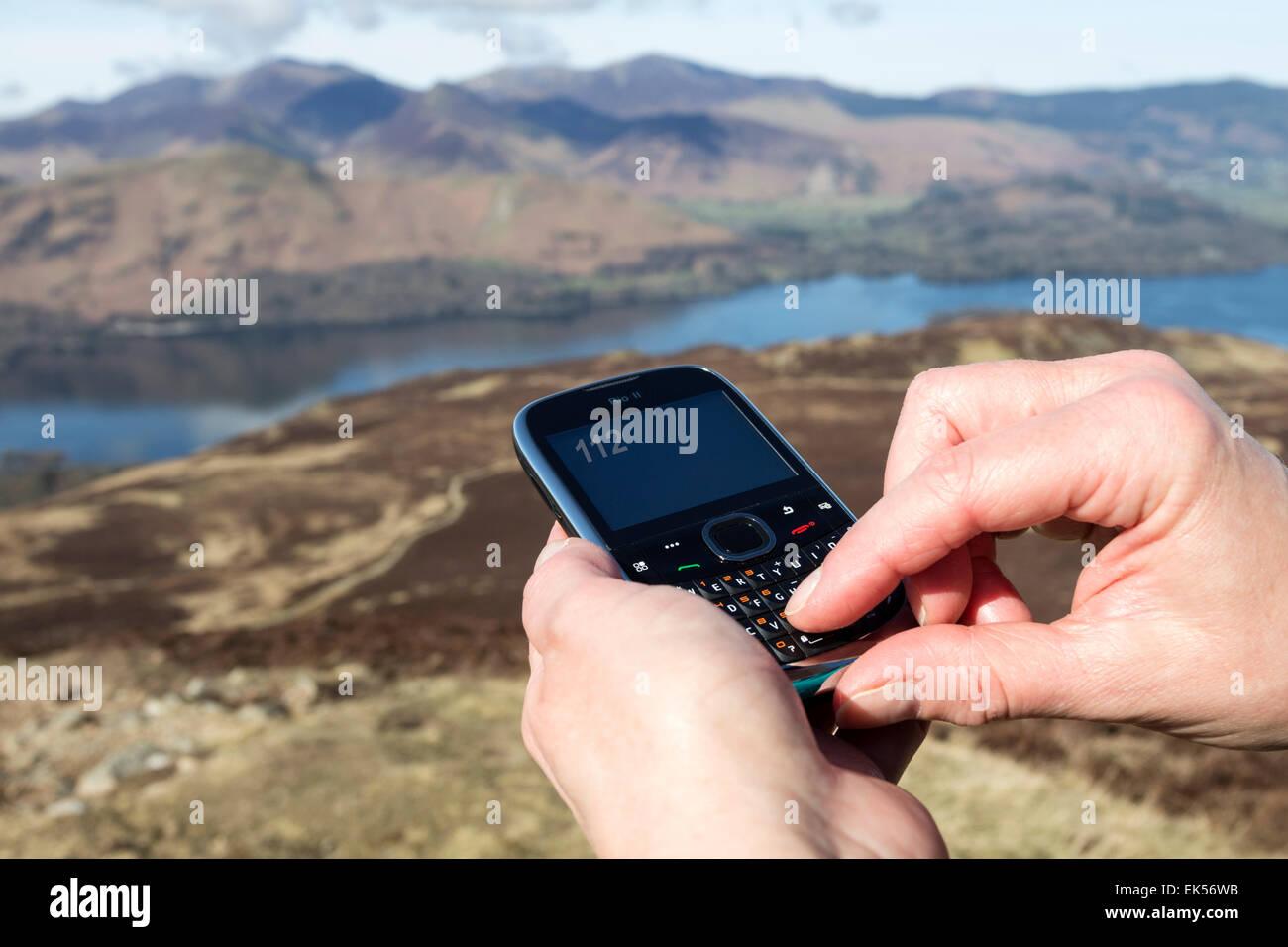 Concept Image de Mobile téléphone utilisé pour composer le 112 dans les montagnes du Lake District Photo Stock