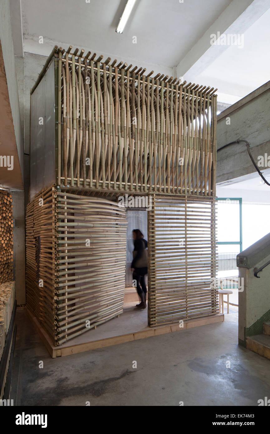 Vue trois-quarts avant avec une personne visible à travers la porte avant. Logement Micro bambou, Kowloon, Photo Stock
