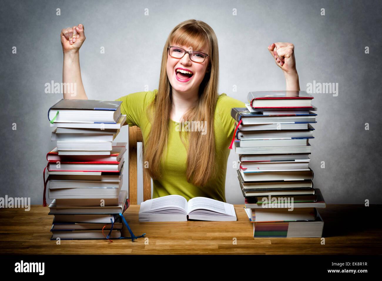 Les jeunes professionnels lycéenne avec des lunettes et des lots de livres à une table Photo Stock