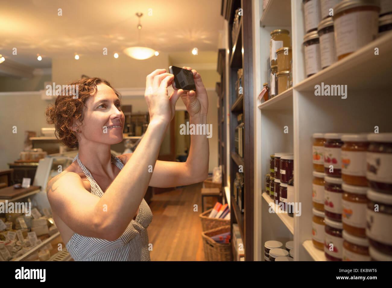Young woman photographing conserve sur smartphone dans l'épicerie bio Photo Stock