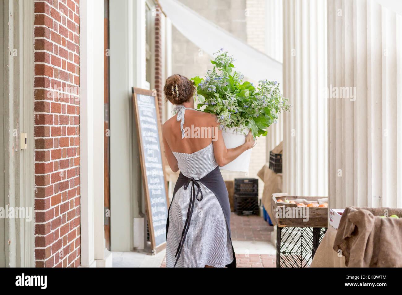 Une femme décharge produits biologiques à l'extérieur de l'épicerie Photo Stock