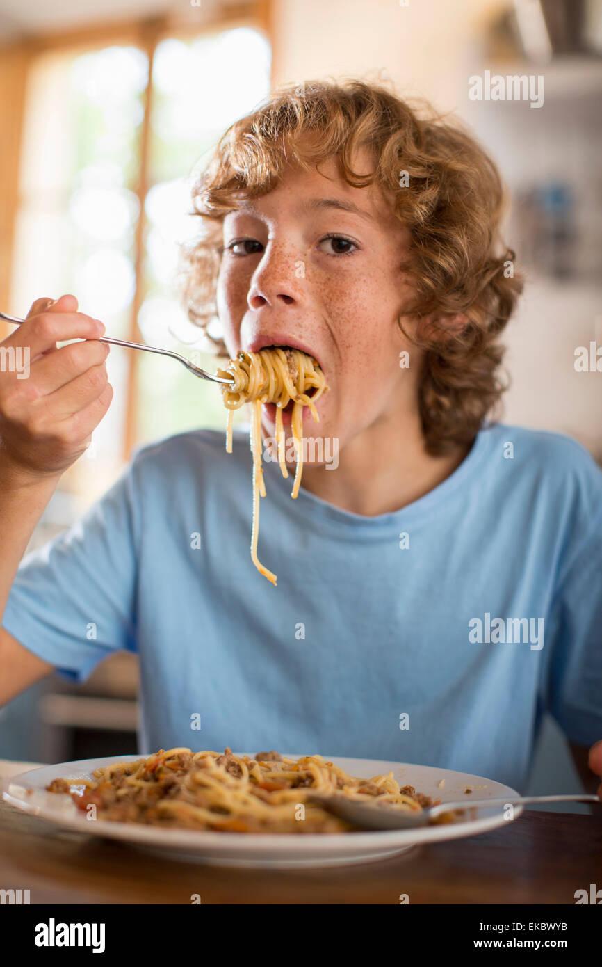 Teenage boy eating spaghetti à table à manger Photo Stock