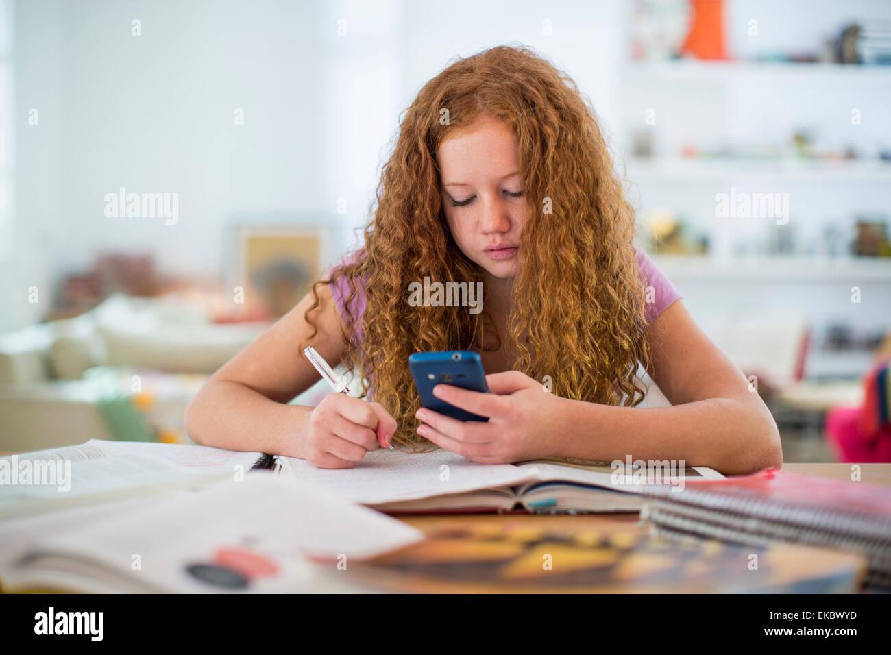 Teenage girl writing notes et using smartphone Photo Stock