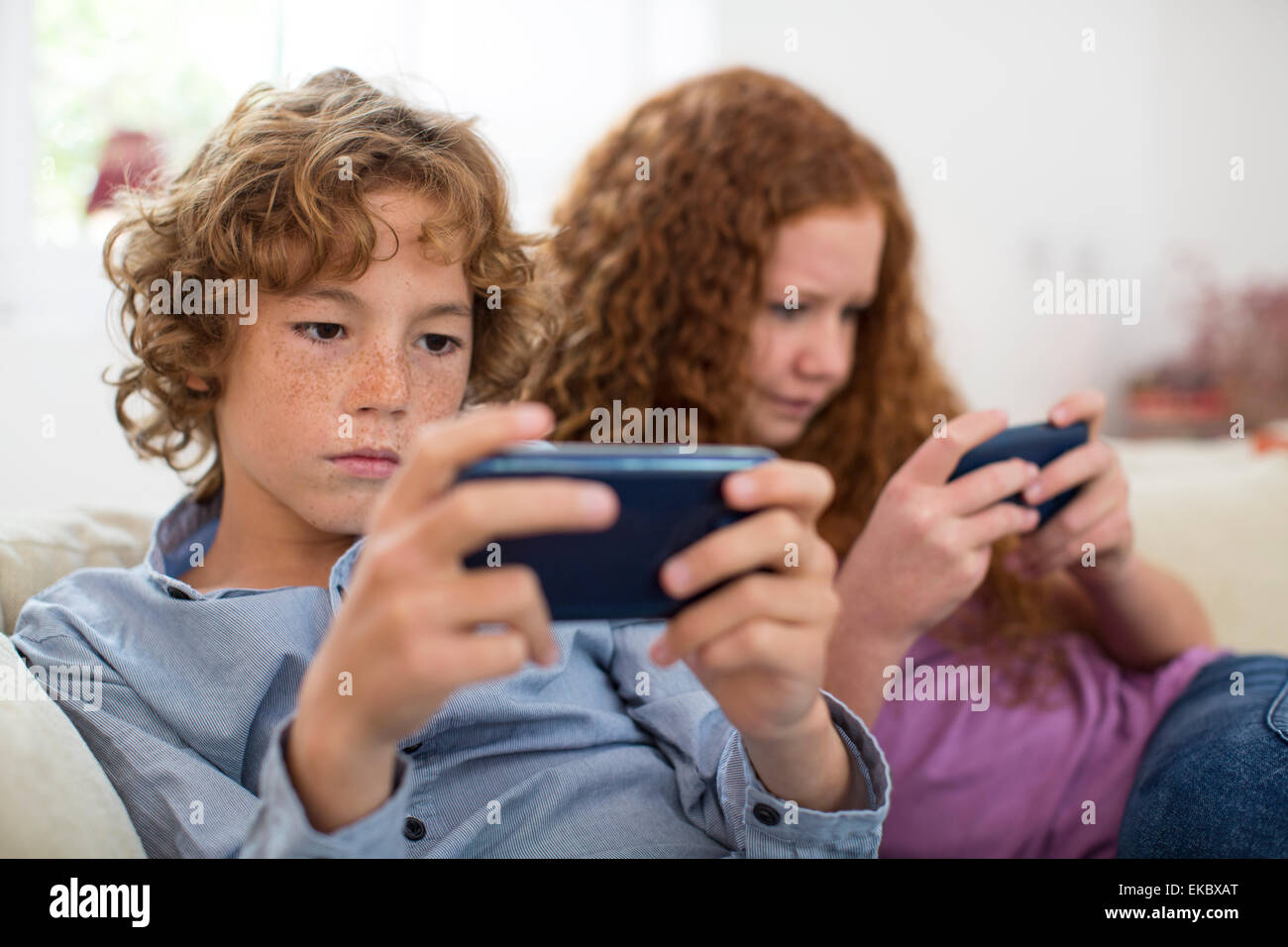 Frères et sœurs jouant avec l'ordinateur de poche sur le plateau de jeu Photo Stock