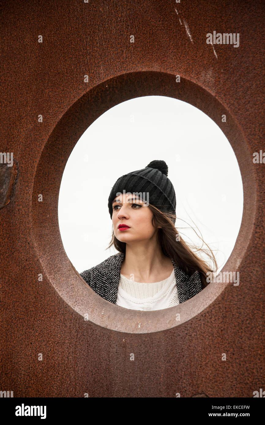 Jeune femme regardant à travers un trou circulaire Photo Stock