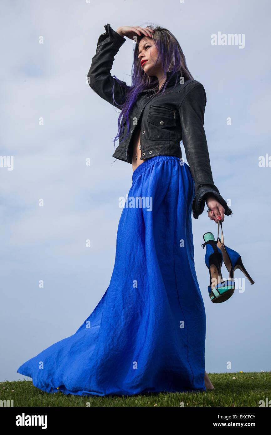 Jeune femme tenant ses chaussures tout en regardant dans la distance Photo Stock