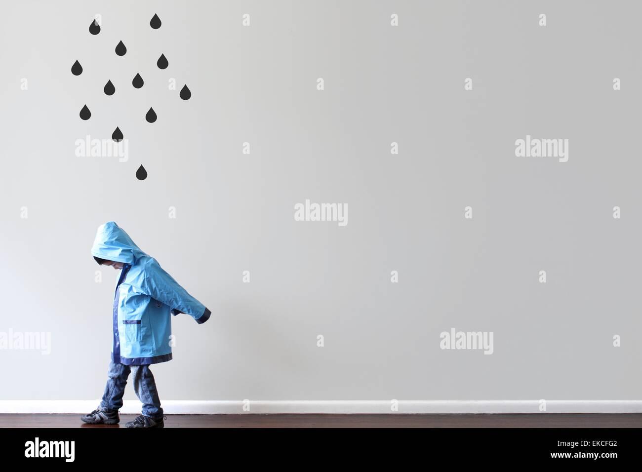 Garçon dans l'imperméable en passant devant un mur avec des gouttes de noir peint sur le mur Photo Stock