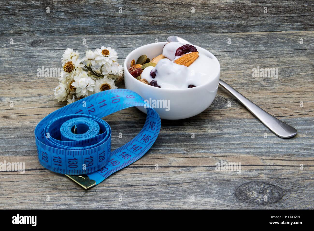 Régime alimentaire Le petit déjeuner avec du yaourt et granola sur fond de bois rustique. Photo Stock