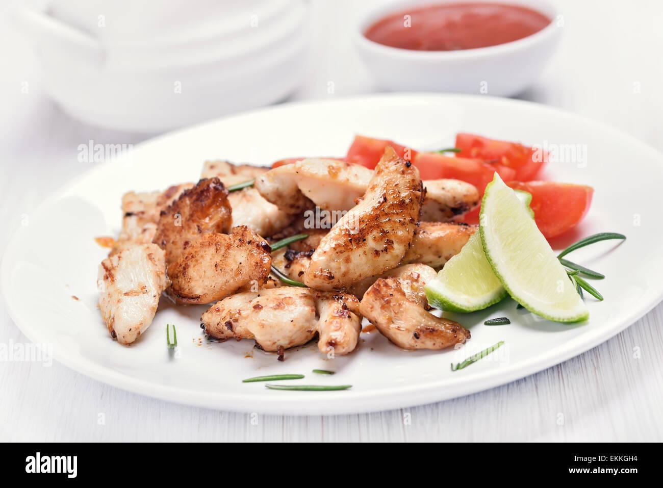 Poulet cuit viandes tranchées avec des légumes sur plaque blanche, faible profondeur de champ Photo Stock