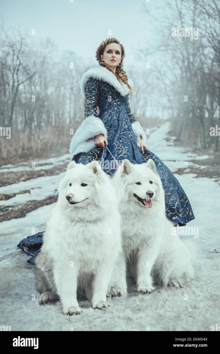 La femme sur l'hiver à pied avec un chien Banque D'Images