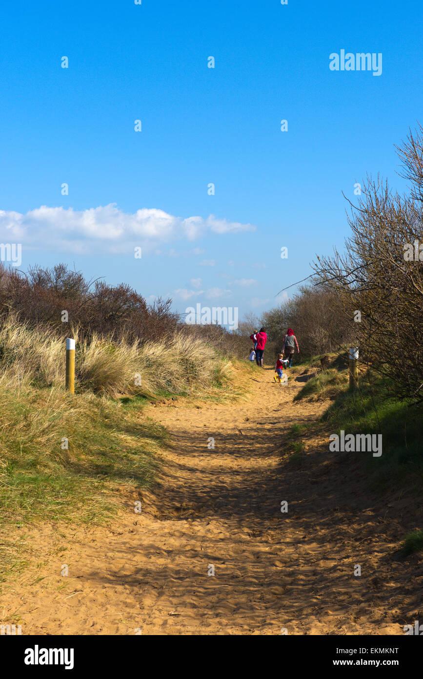 Les gens qui marchent vers le bas jusqu'à la plage à travers les dunes de la réserve naturelle locale Berrow, Somerset Banque D'Images