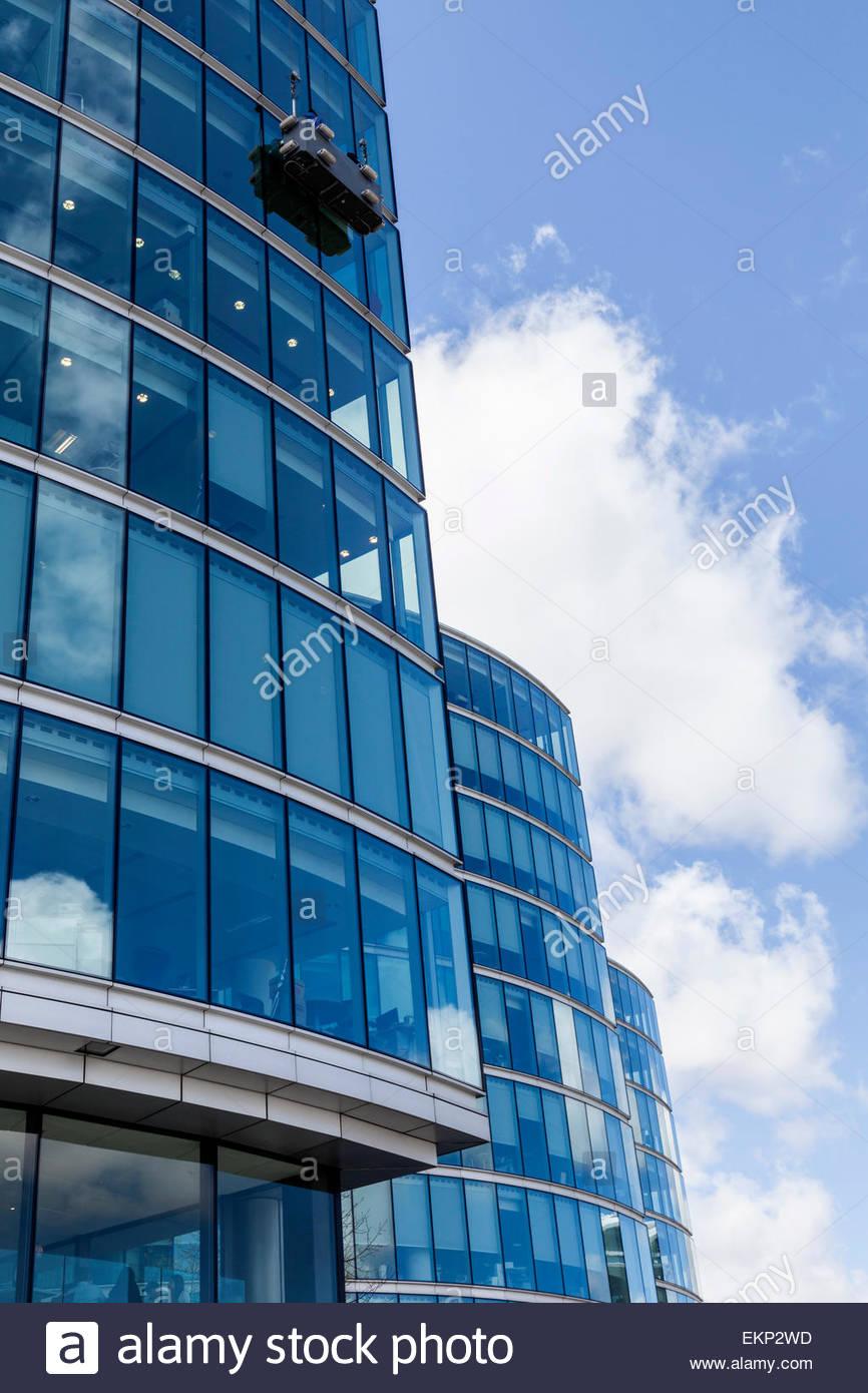 Nettoyage des fenêtres d'un grand immeuble de bureaux de l'utilisation d'un berceau. Photo Stock