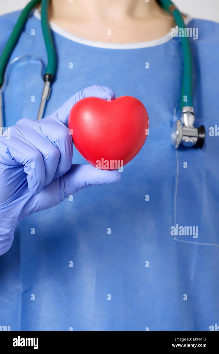 Coeur rouge dans la main d'un médecin Photo Stock