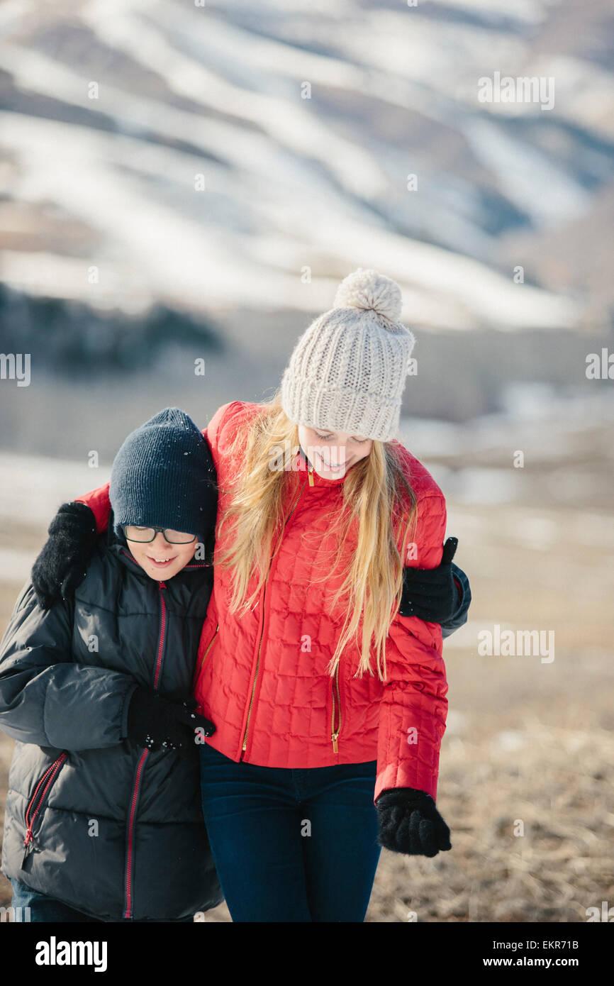 Un frère et une sœur serrant et rire ensemble à l'extérieur. Photo Stock