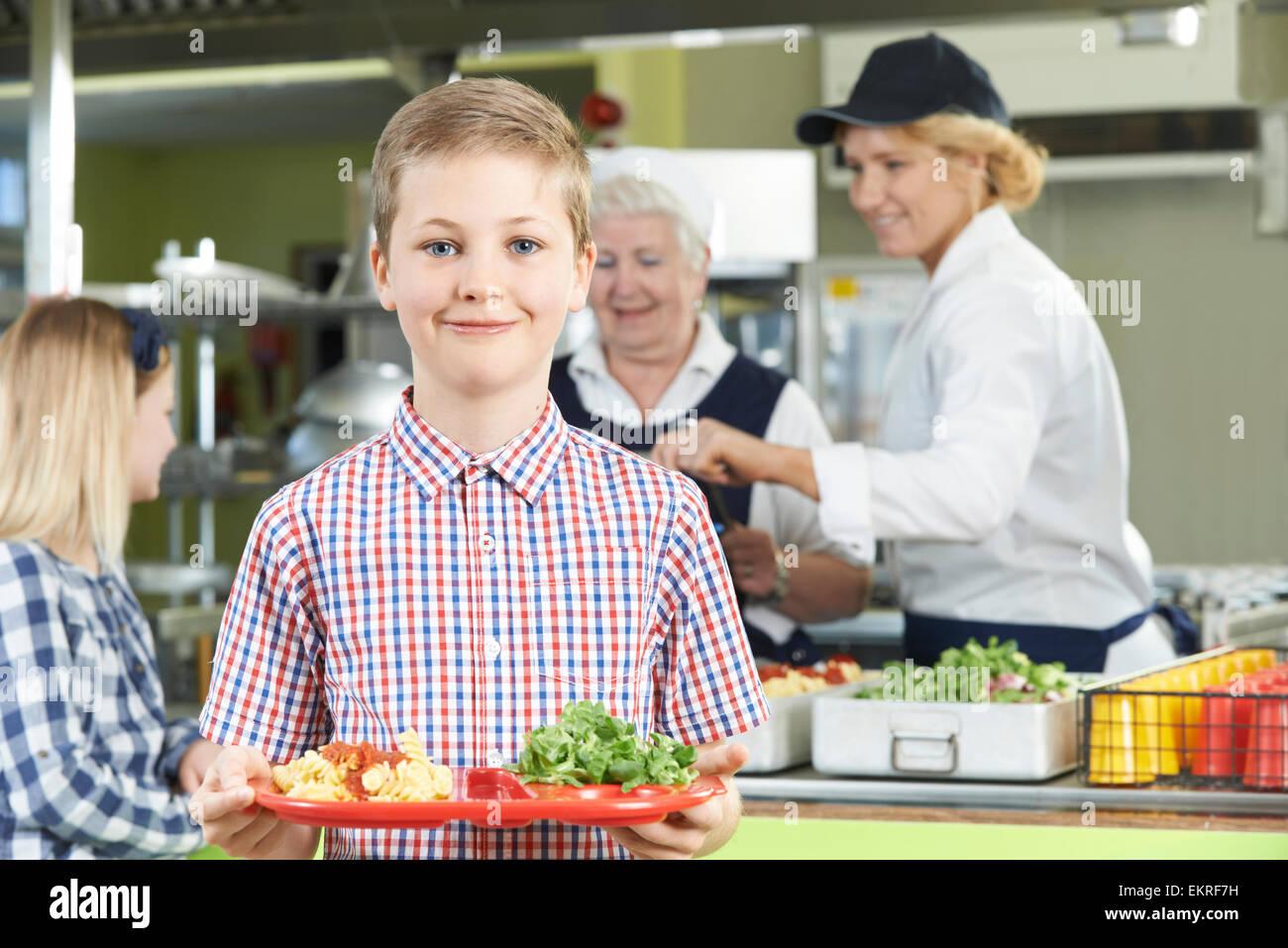 Élève de sexe masculin en bonne santé avec le déjeuner dans la cafétéria de l'école Photo Stock