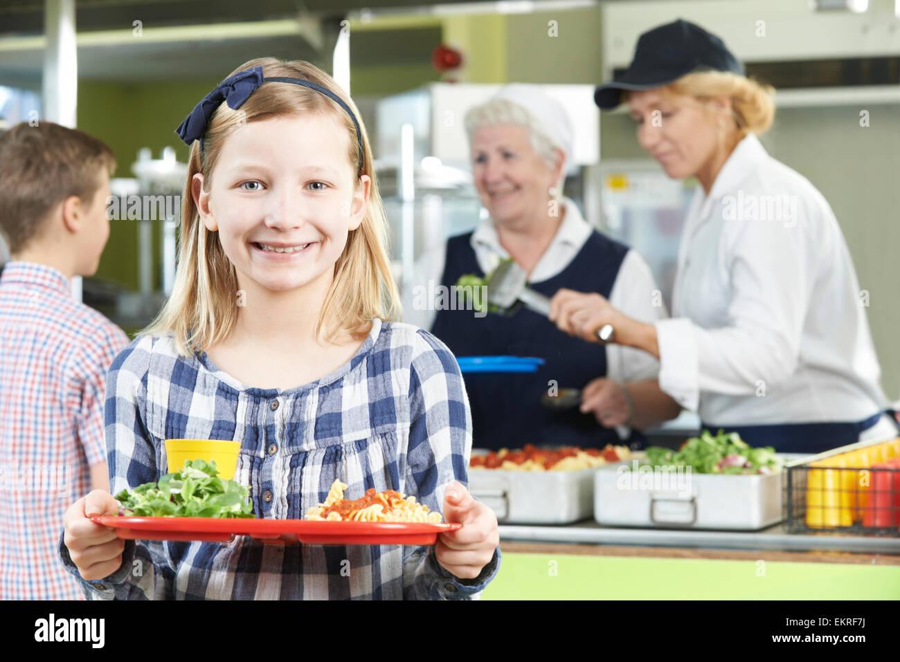 Élève de sexe féminin avec dîner santé en cantine scolaire Photo Stock