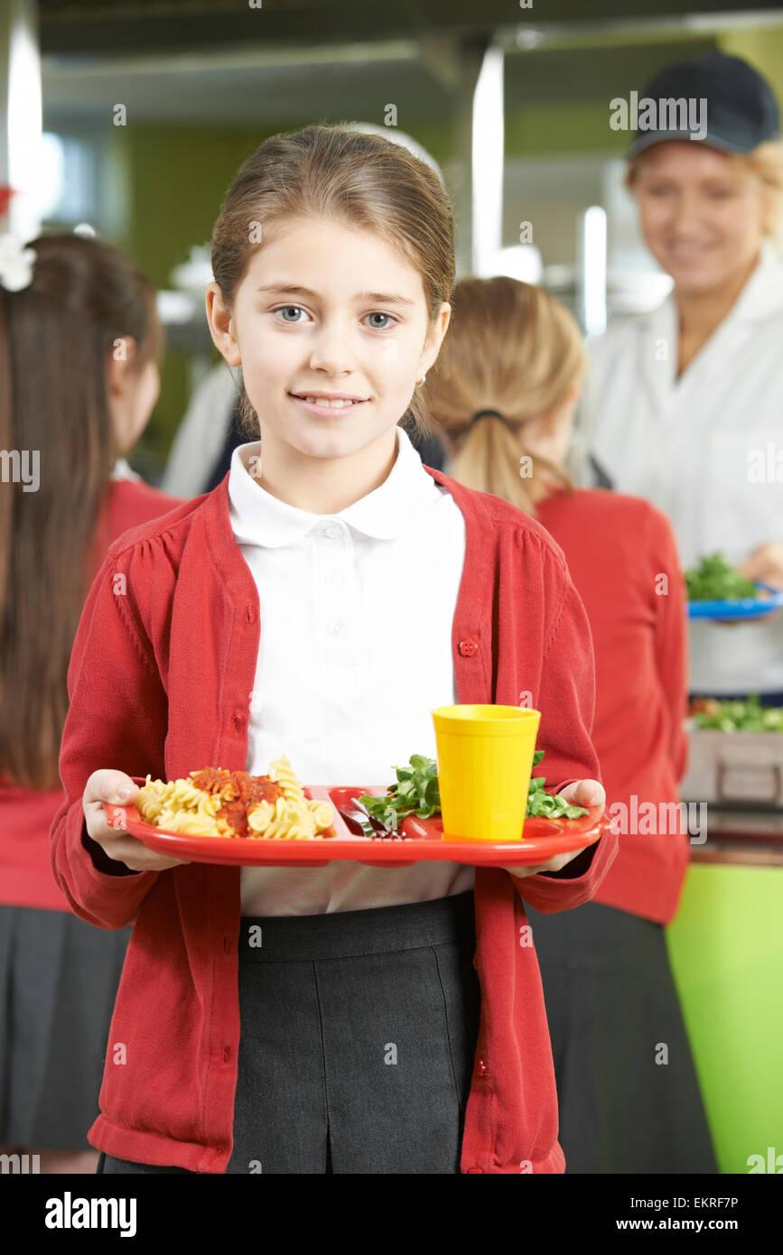 Élève de sexe féminin avec déjeuner sain dans la cafétéria de l'école Photo Stock
