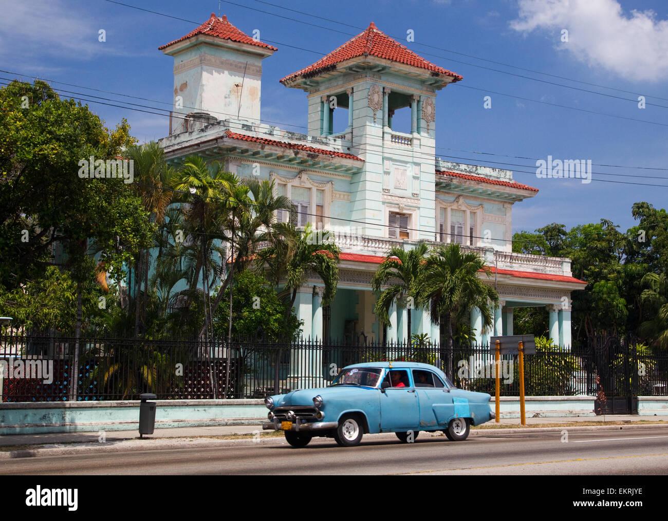 Un classique american retro automobile passe une villa de style colonial à La Havane Photo Stock