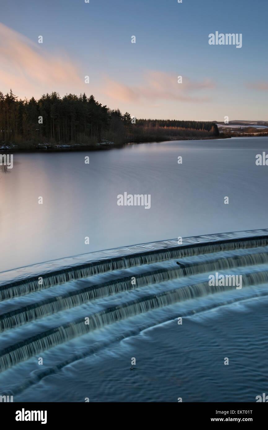 Coucher du soleil à Fewston d'hiver, avec le trop-plein du réservoir à l'avant-plan. Banque D'Images