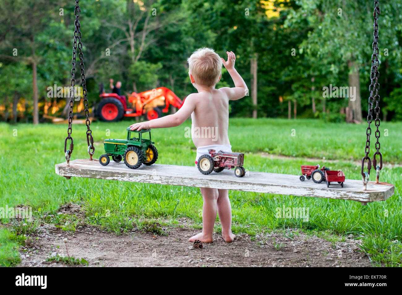 Boy waving to daddy sur le tracteur Photo Stock