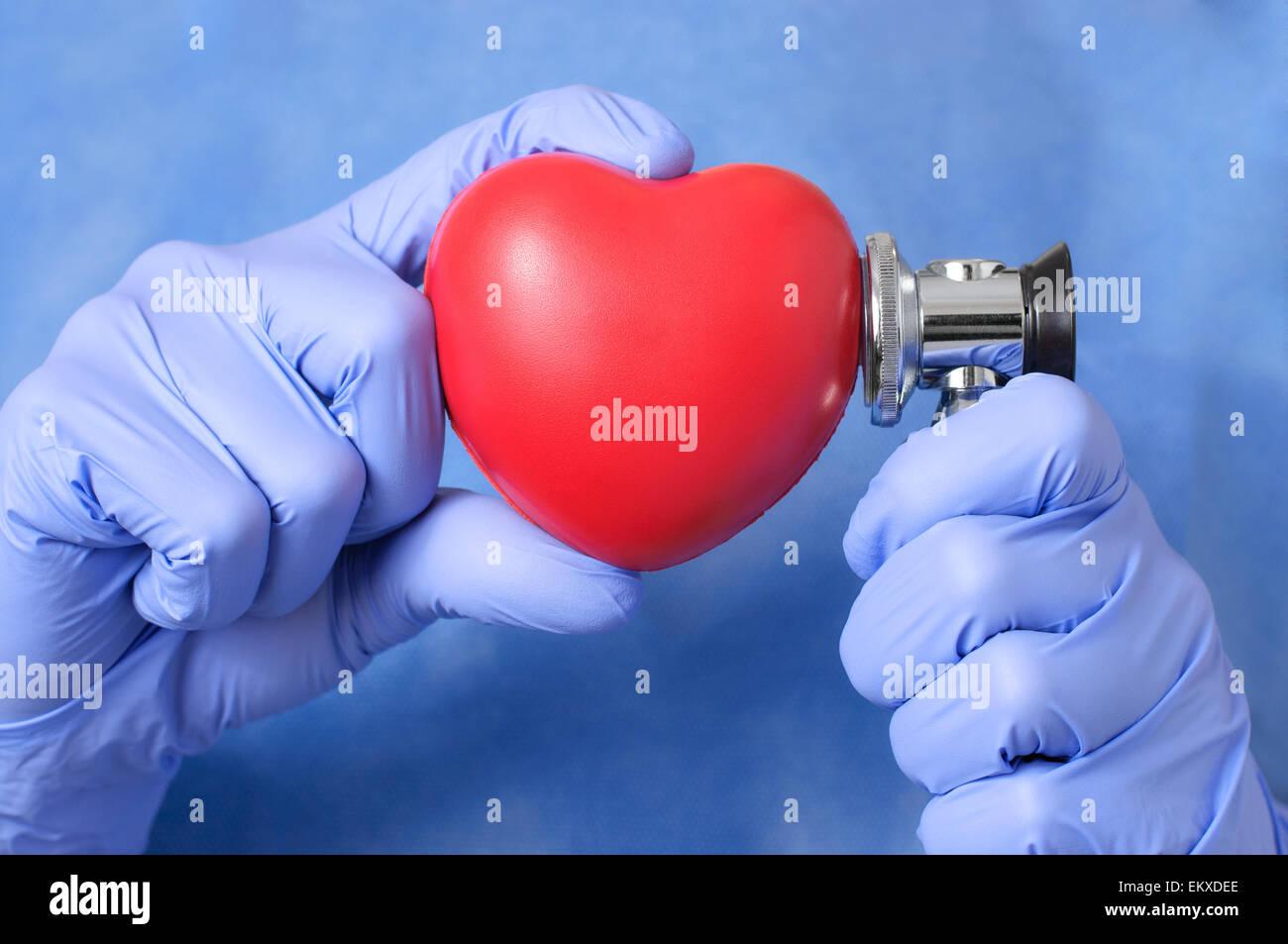 Coeur rouge et stéthoscope dans la main d'un médecin Photo Stock