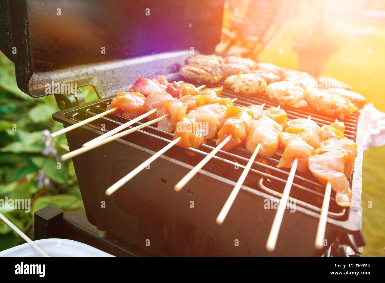 Des hamburgers et des viandes grillées sur le barbecue satays prêt pour les repas en plein air d'été Photo Stock