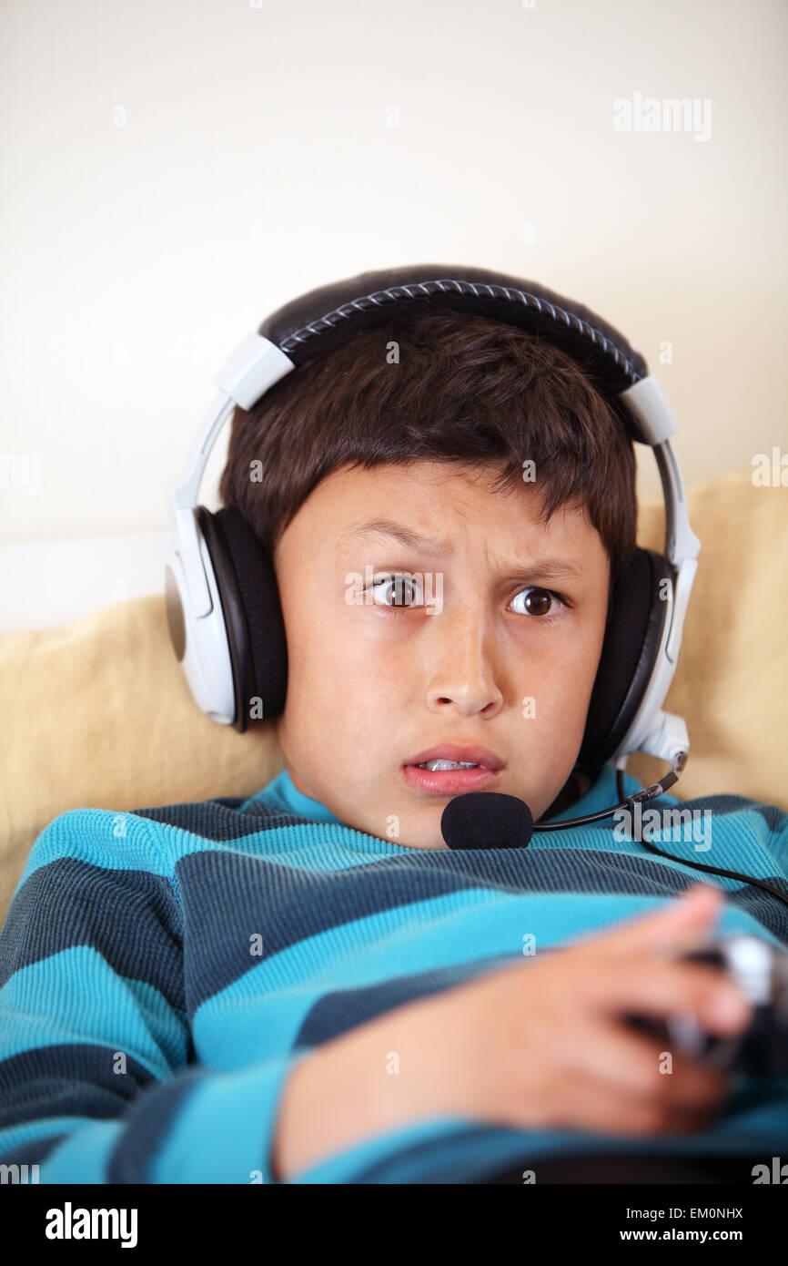 Les jeunes confus jeux vidéos avec ses amis avec casque et microphone with copy space Photo Stock