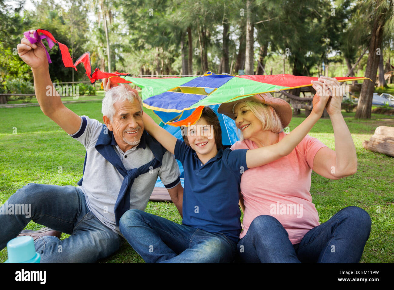 Happy boy avec les grands-parents holding kite au camping Photo Stock