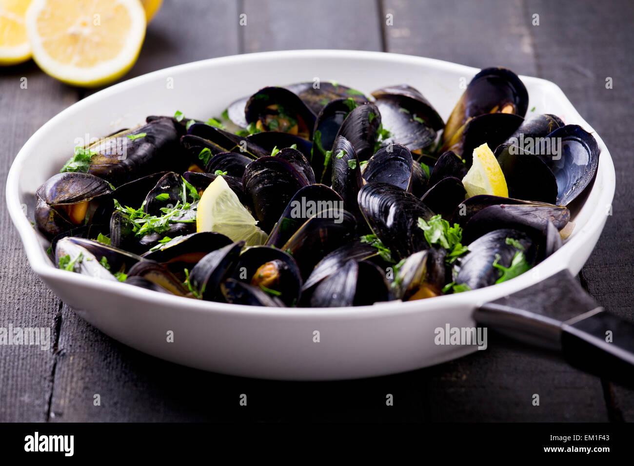 Les moules fraîches cuites dans une casserole avec le vin et les herbes Photo Stock