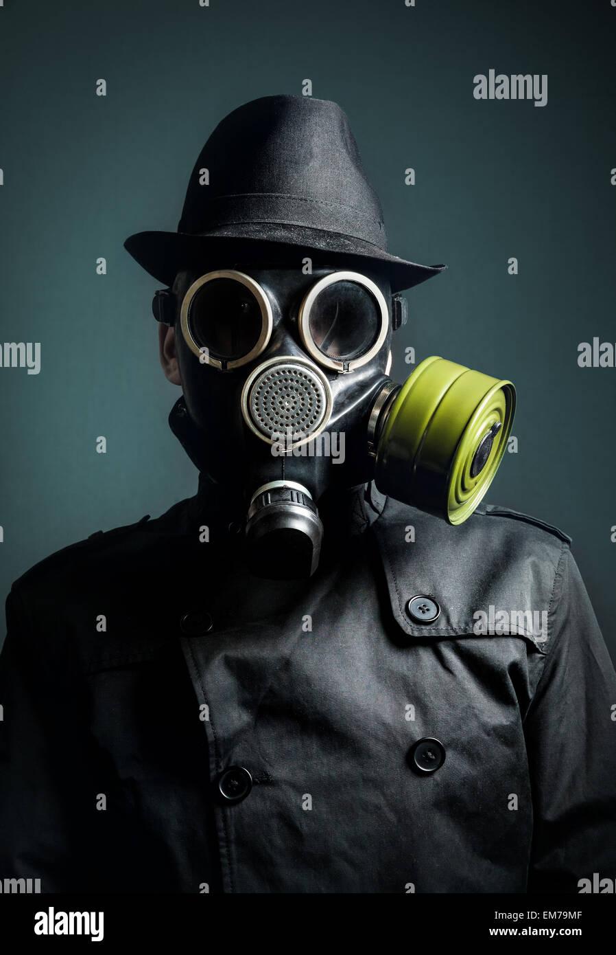 L'homme en masque à gaz, imperméable et chapeau noir à fond sombre Photo Stock