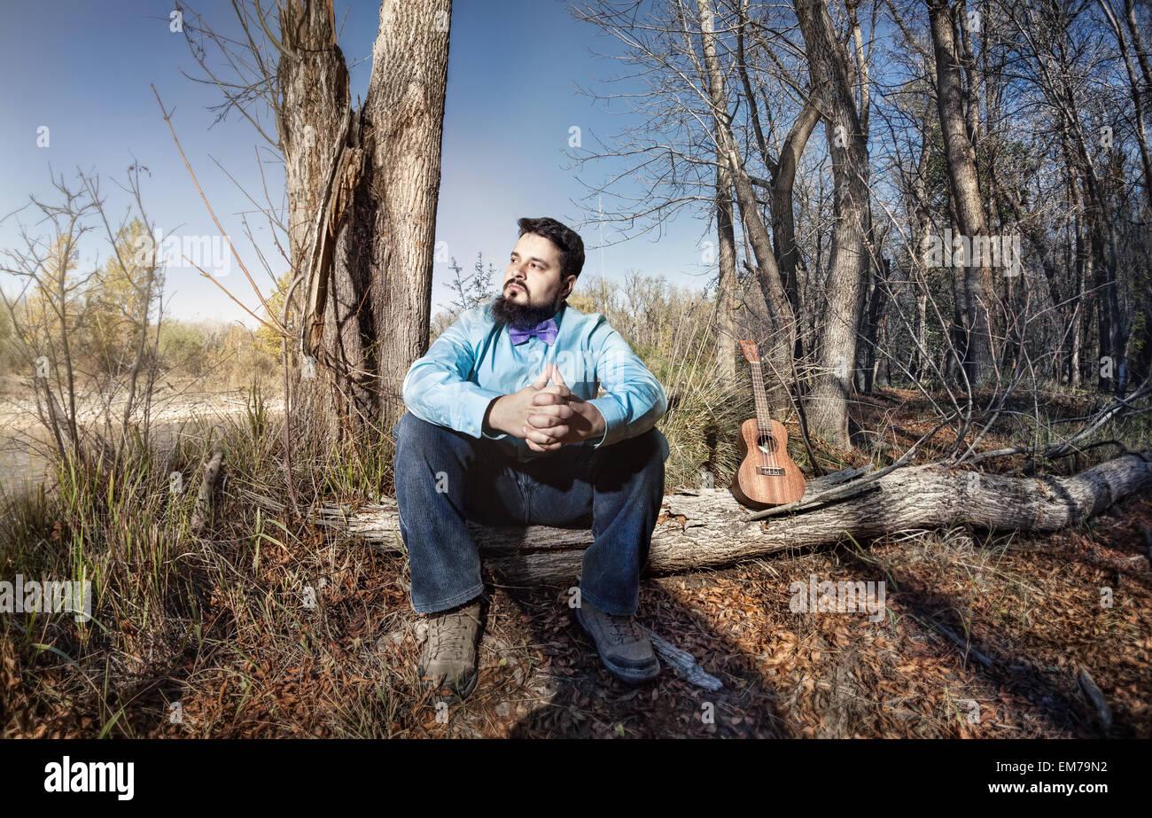 L'homme en chemise bleue avec papillon et ukulele sur le tronc de l'arbre dans la forêt Photo Stock