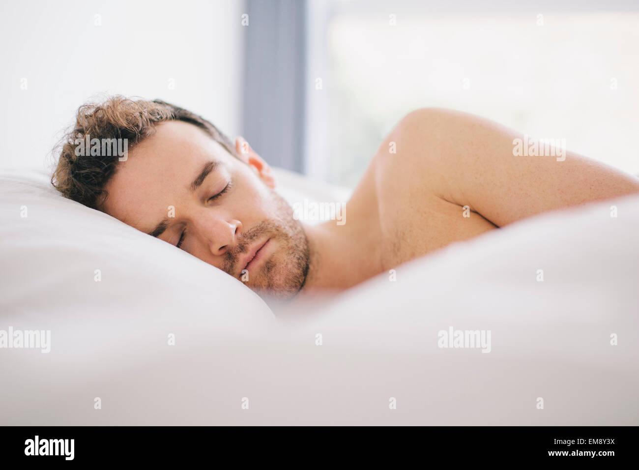 Jeune homme étendu sur le côté endormi dans le lit Photo Stock