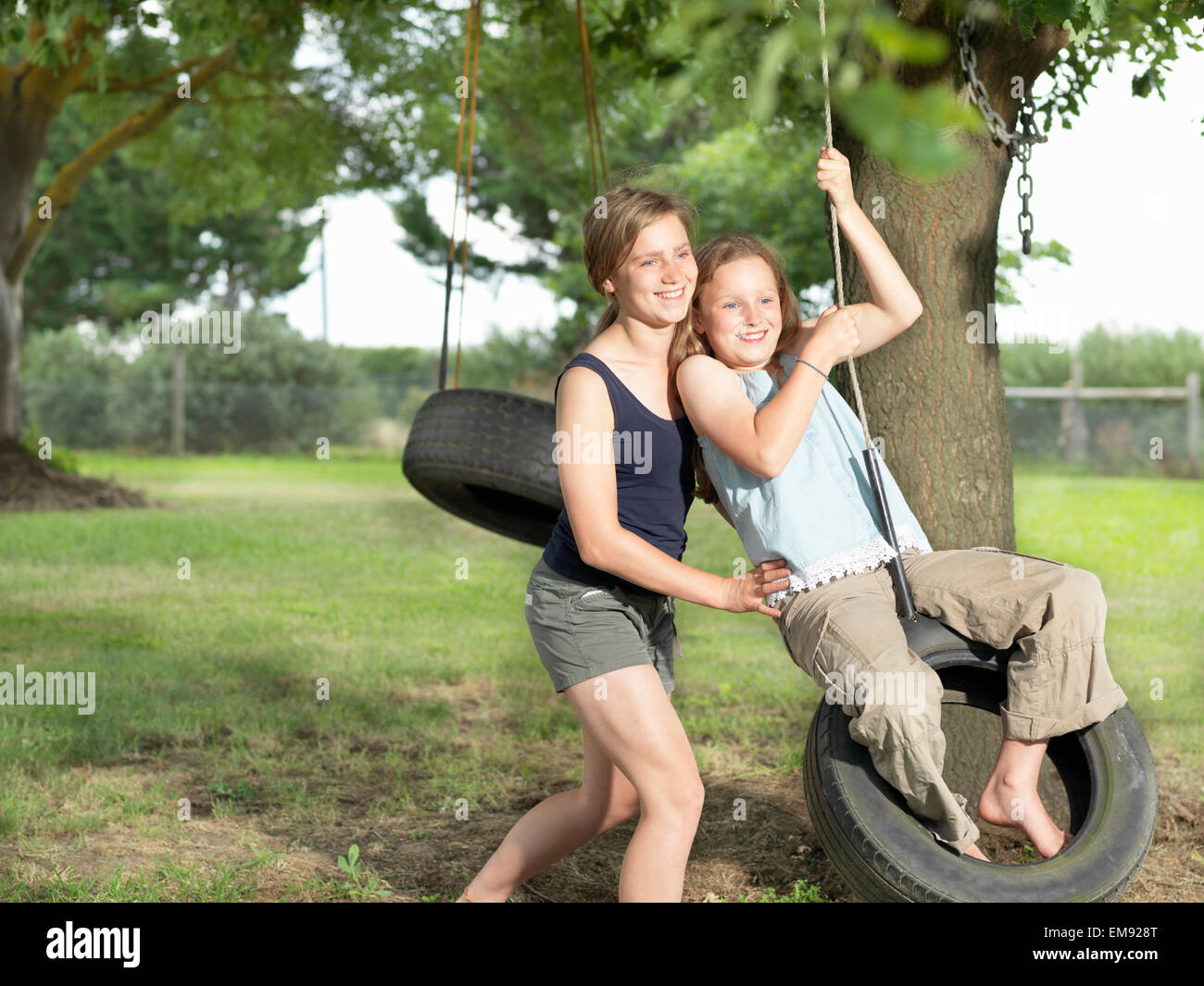 En poussant sa sœur adolescente sur balançoire pneu Banque D'Images