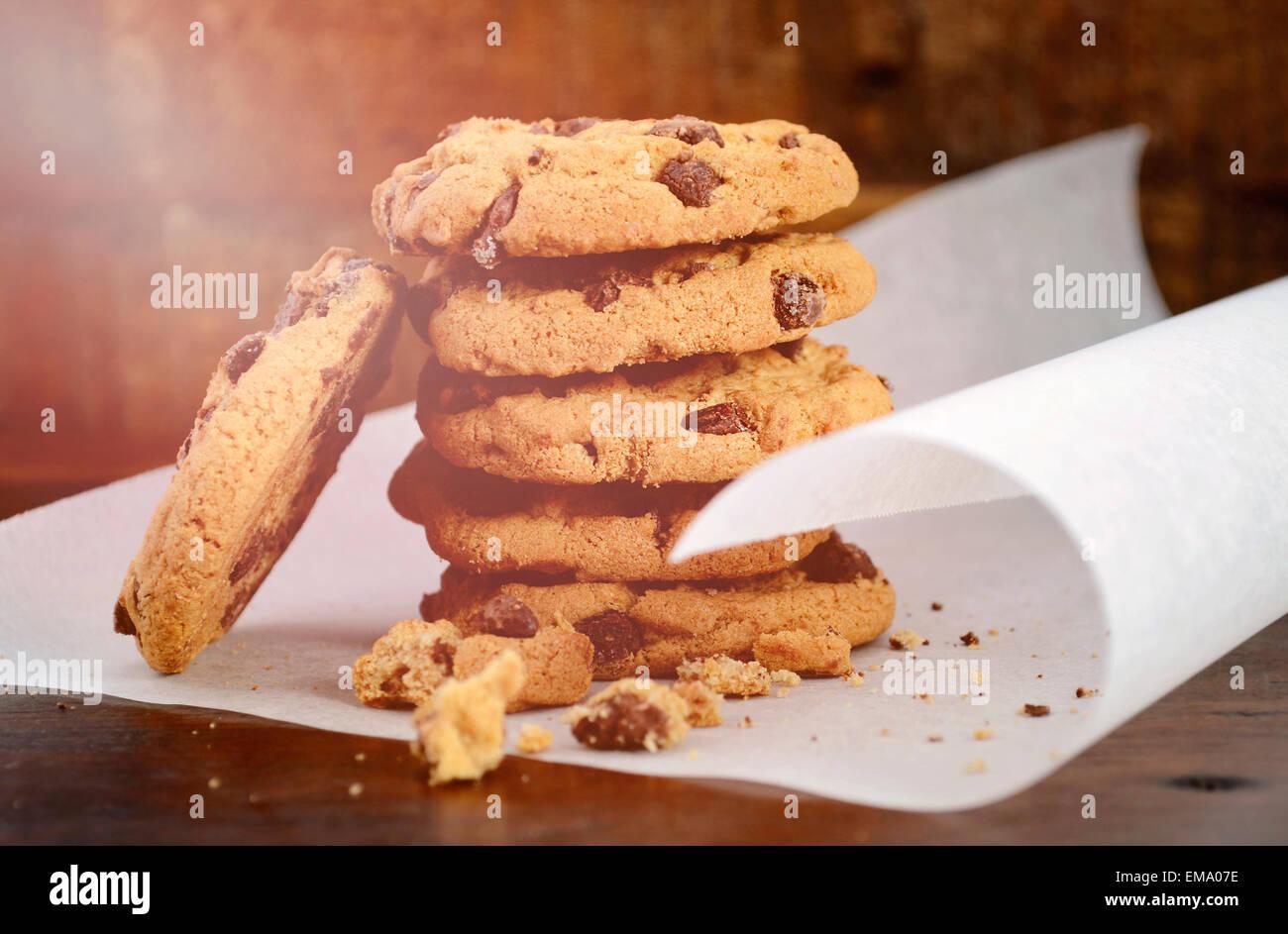 Pile de cookies aux pépites de chocolat sur du papier sulfurisé curling blanc contre un fond en bois sombre, Photo Stock
