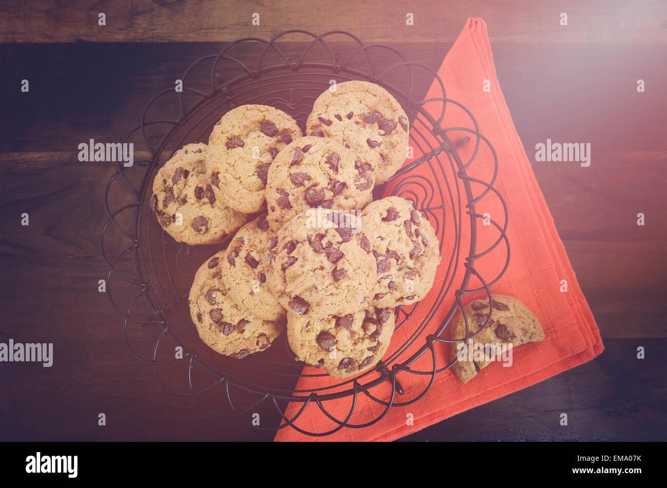 Chocolate Chip cookies sur vintage grille de cuisson avec serviette orange sur fond en bois sombre, avec des filtres Photo Stock