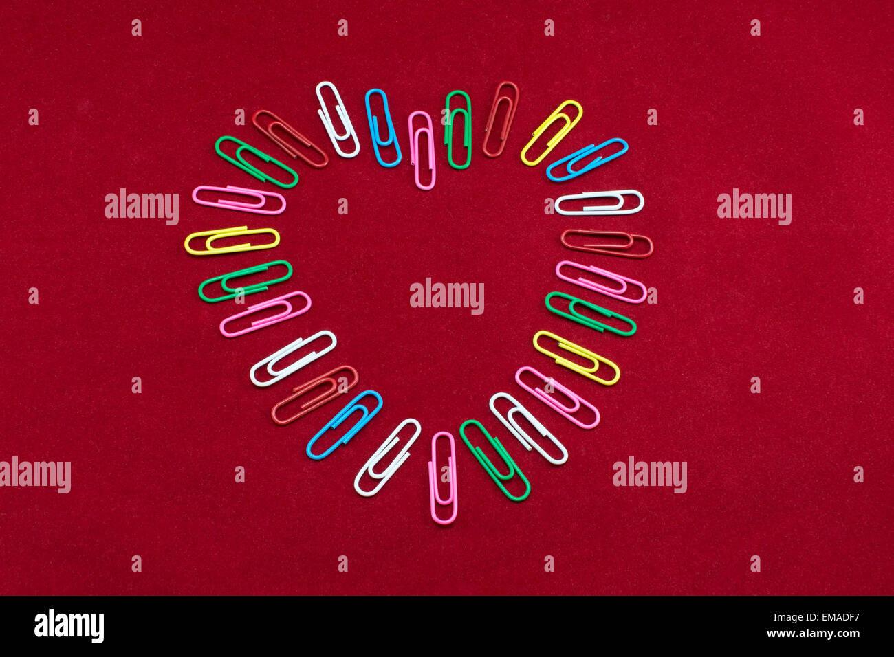 Clips de papier de couleur disposés pour former la forme d'un cœur. Photo Stock