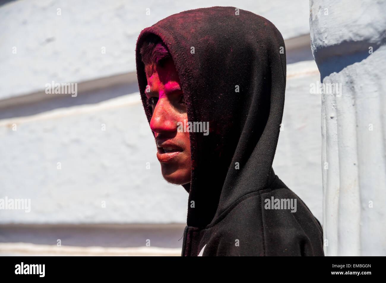 Adolescent népalais avec visage peint en rouge et un sweat noir lors du festival holi Photo Stock