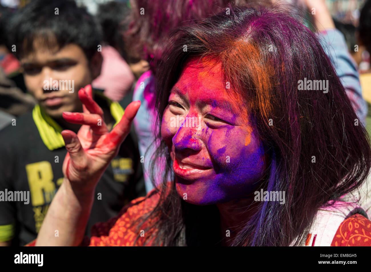 Asian woman with face peinte en rouge signe l'appareil photo pendant le festival holi Photo Stock