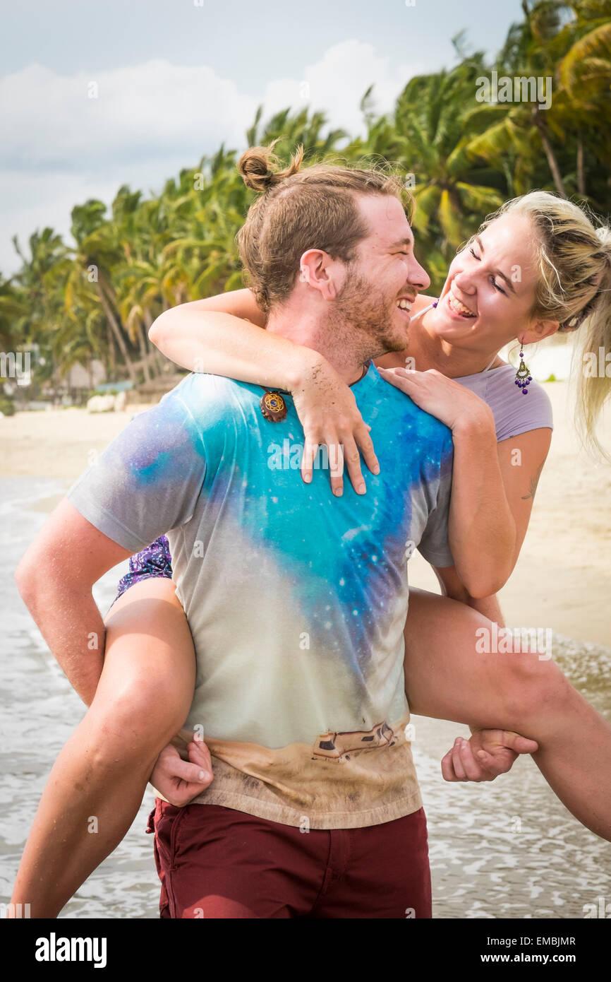 Jeune couple, l'homme et de la femme dans l'amour, l'exécution de piggyback ride sur une plage, Photo Stock