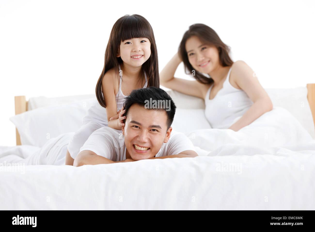 Père a la jeune fille et sa mère dans le lit de la chambre à coucher Banque D'Images