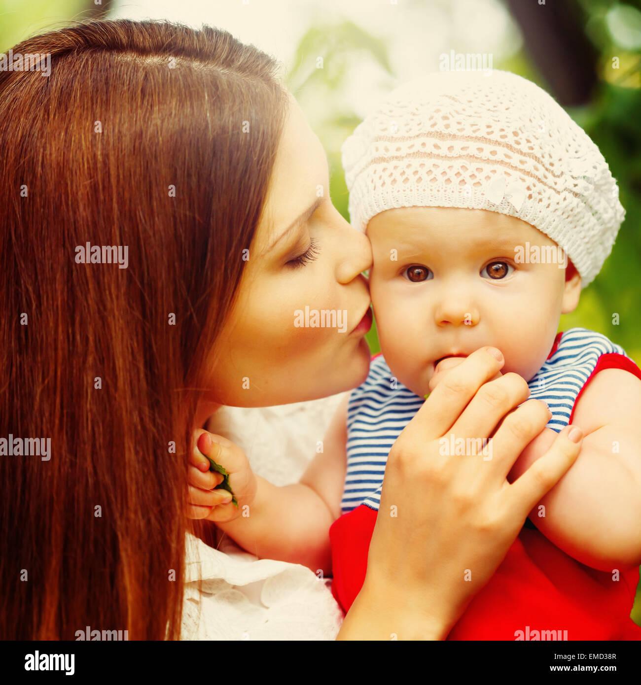Surpris Toddler Baby Girl sitting on Mom's Hands, à la recherche en appareil photo. Mère embrassant Photo Stock