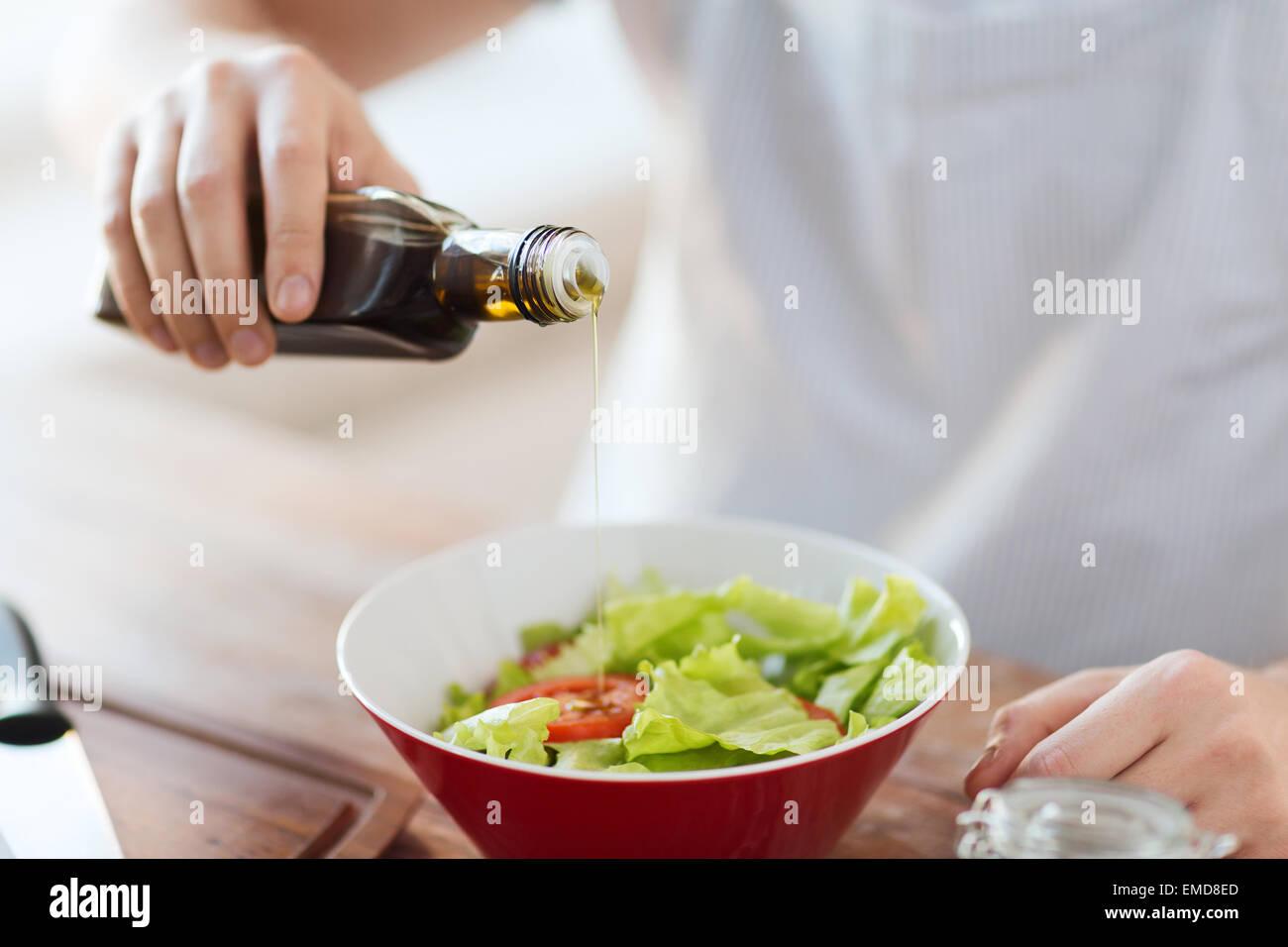 Les mains de l'assaisonnement dans un bol à salade Photo Stock