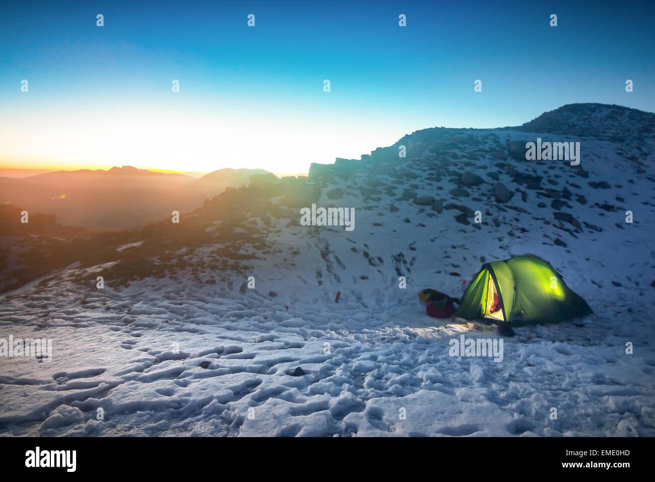 Tente éclairée et le coucher du soleil dans les montagnes Photo Stock