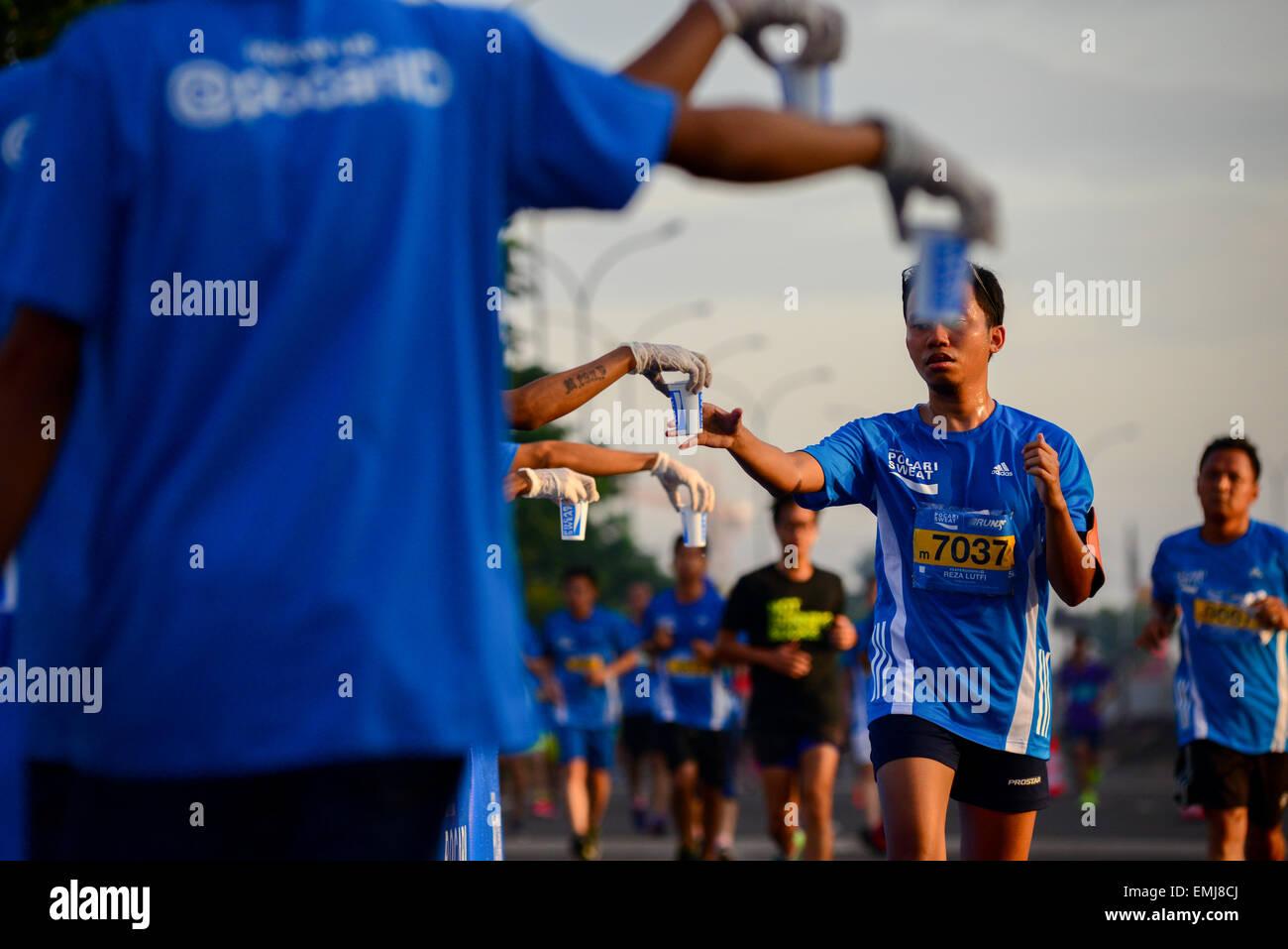 Porteur de prendre un verre dans un rafraîchissement tout en tournant au Pocari Sweat course Run 2015 dans Photo Stock