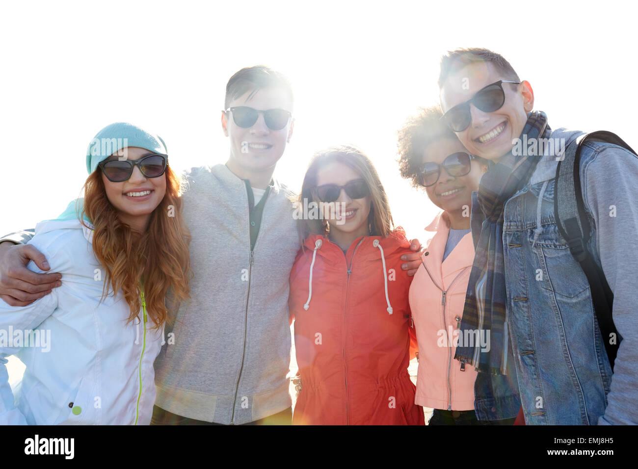 Heureux amis adolescents dans les tons hugging on street Photo Stock